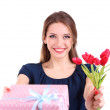 Attractive woman with gift box and flowers, isolated on white — Stock Photo