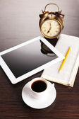 Tablett, tidning, kopp kaffe och väckarklocka på träbord — Stockfoto