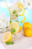 Glass of cocktail with lemon and mint on table on light blue background — Stock Photo