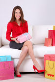 Beautiful young woman sitting on sofa with shopping bags and gift box on gray background — Stockfoto