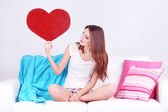 Beautiful young woman sitting on sofa with decorative heart on gray background — Stock Photo