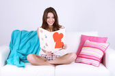 Beautiful young woman sitting on sofa with card on gray background — Stock Photo