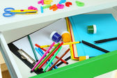 School supplies in open desk drawer close up — Stock Photo