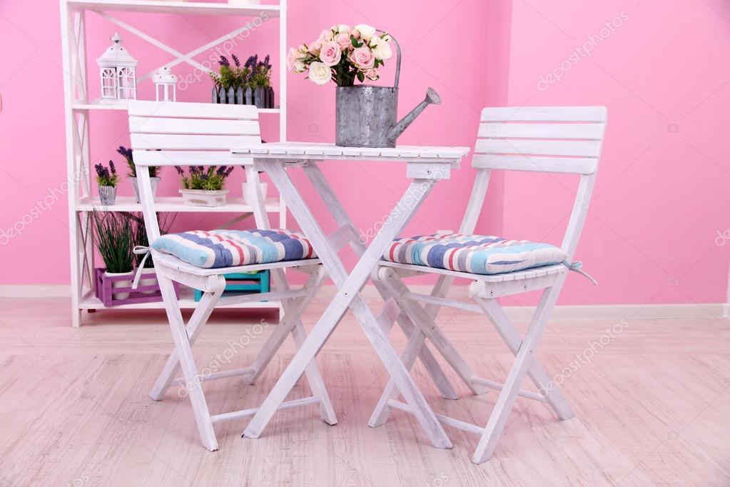 Sedie da giardino e tavolo con fiori sugli scaffali su for Tavolo da giardino con sedie