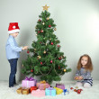 Kids decorating Christmas tree with baubles in room — Stock Photo