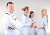 Doctor parado frente a los compañeros de trabajo sobre fondo gris — Foto de Stock