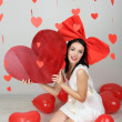 Attractive young woman with big heart and balloons in room on Valentine Day — Stock Photo #40779577