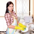Beautiful young womwashing dishes in kitchen — Stock Photo #40780213