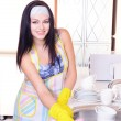 Beautiful young womcleans in kitchen — Stock Photo #40780241