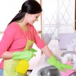 Beautiful young womcleans in kitchen — Stock Photo #40780245