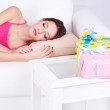 Beautiful young woman sleeping on sofa near table with gifts and flowers, close up — Stock Photo #40781955