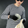 Stock Photo: Thief with bag on dark background