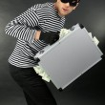 Thief with metal briefcase on dark background — Stock Photo