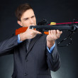 Young businessman with crossbow, on dark background — Stock Photo
