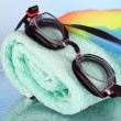 Set for pool: swim cap, goggles and towel on blue background — Stock Photo #40789705