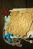 Papel viejo con accesorios de mar, aislado sobre fondo de madera — Foto de Stock