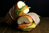 Fresh and tasty sandwich on wooden table on black background — Stock Photo