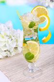 Copo de coquetel com limão e hortelã sobre mesa de luz de fundo azul — Fotografia Stock