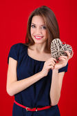 Attractive woman with wicker heart, on red background — Stockfoto