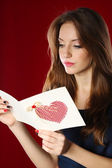 Attractive woman with postcard, on red background — Stockfoto