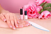 Beautiful woman hands with french manicure and flowers on table on pink background — Stock Photo