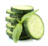 Gesneden verse komkommer met basilicum, geïsoleerd op wit — Stockfoto
