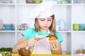 Little girl decorating cupcakes in kitchen at home — ストック写真