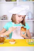 Kleine mädchen schmücken cupcakes in küche zu hause — Stockfoto