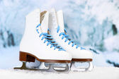 Figure skates on winter background — Stock Photo