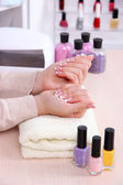 Young woman getting manicure in beauty salon — Stock Photo
