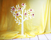 Dekorative baum mit dekorativen herzen auf holztisch auf farbigem stoff hintergrund — Stockfoto