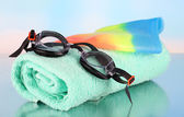 Set for pool: swim cap, goggles and towel on blue background — Stock Photo