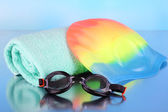 Set for pool: swim cap, goggles and towel on blue background — Foto Stock