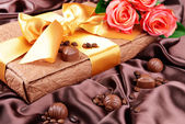 Delicious chocolates in box with flowers on brown background — Stockfoto