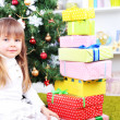 Little girl with presents near Christmas tree in room — Stock Photo #40814351