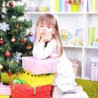 Little girl with presents near Christmas tree in room — Stock Photo #40814353