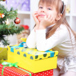 Little girl with presents near Christmas tree in room — Stock Photo #40814369