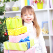 Little girl with presents near Christmas tree in room — Stock Photo #40814377