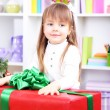 Little girl setting on big present box in room — Stock Photo #40814395