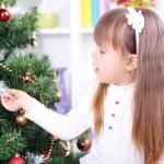 Little girl near Christmas tree in room — Stock Photo