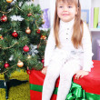 Little girl setting on big present box near Christmas tree in room — Stock Photo #40814427