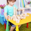 Little girl plays with construction blocks sitting at table in room — Stock Photo #40814605