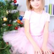 Little girl sitting on big present box near Christmas tree in room — Stock Photo
