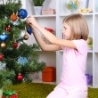 Little girl decorating Christmas tree in room — 图库照片
