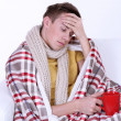 Stock Photo: Guy wrapped in plaid lies on sofon white background