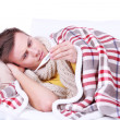 Stock Photo: Guy wrapped in plaid lies on sofis ill