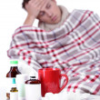 Guy wrapped in plaid sitting on sofa is ill — Stock Photo #40817801