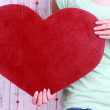 Female holding big red heart on wooden background — Stock Photo