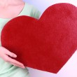 Female holding big red heart on bright background — Stock Photo #40819495
