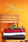 Ručníky a květiny na dřevěné židli na oranžovém pozadí — Stock fotografie